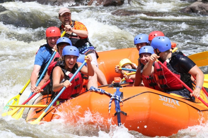 Rafters paddling whitewater