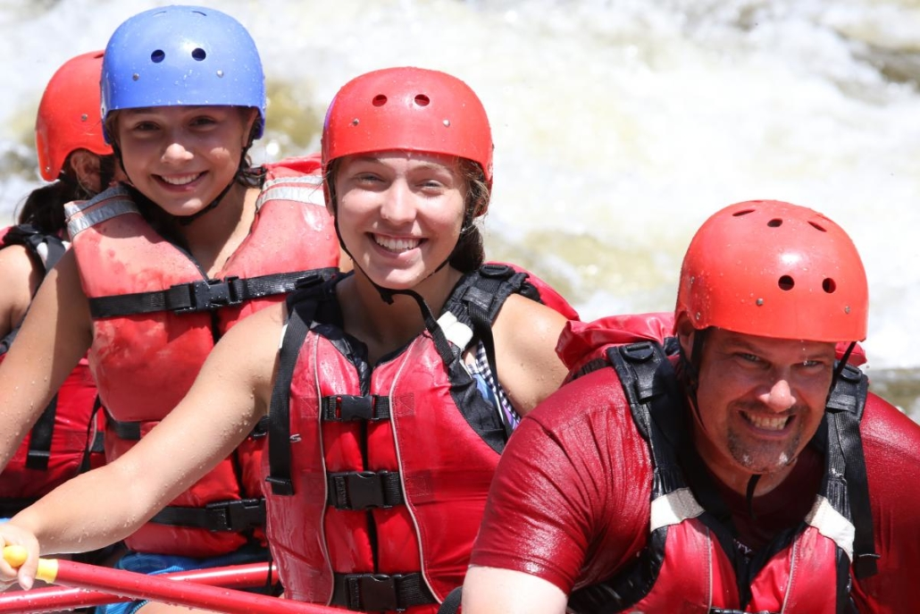 Young rafters smiling while dad grimaces